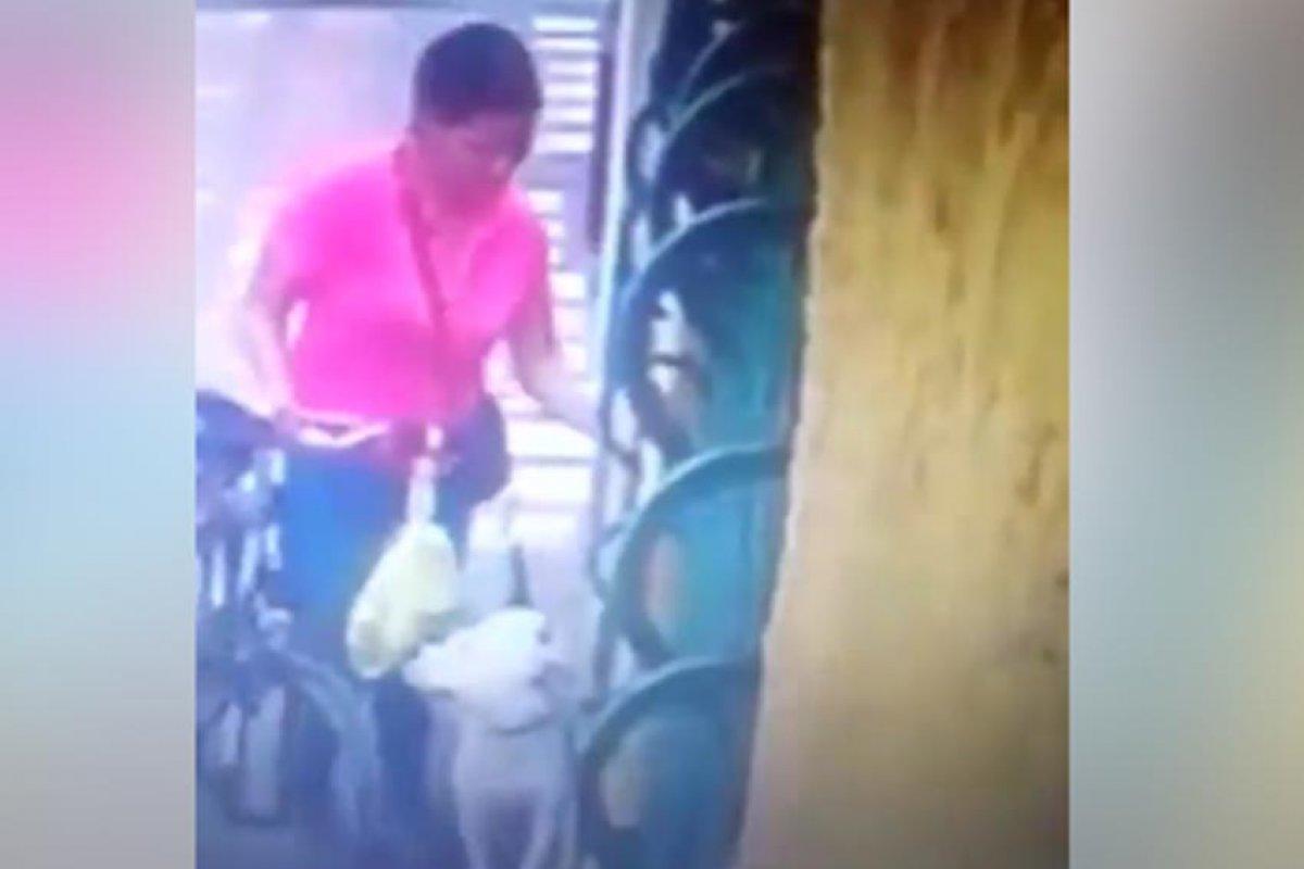 Una mujer camina por la calle, en una mano lleva su bicicleta y en la otra la correa con su perro.